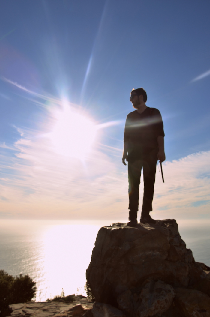 Man standing on mountain with sunset