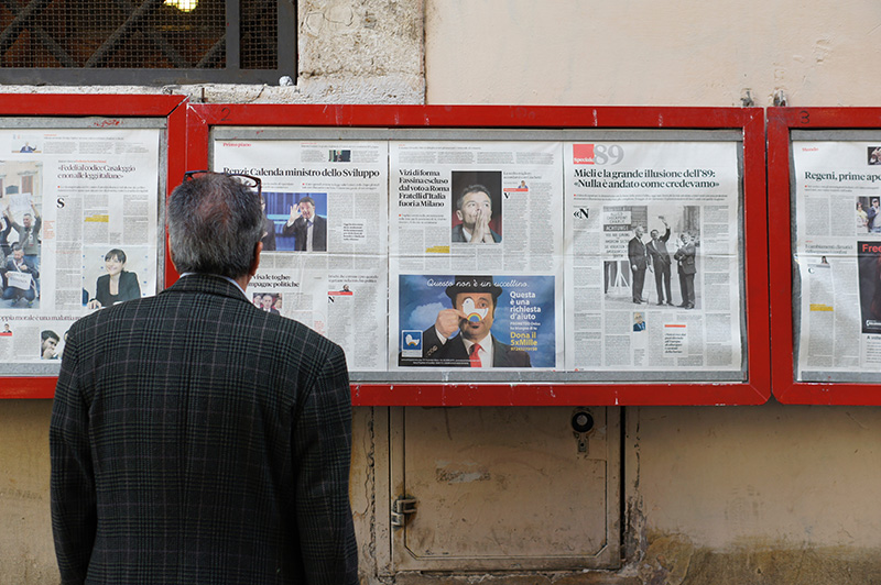 Man reading a news from newspapers hanging on the wall